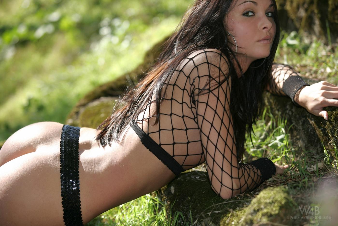 Возбужденная темненькая девушка Divinity Love в черном сетчатом верхе обнажает возбужденную бритую пилотку на поляне