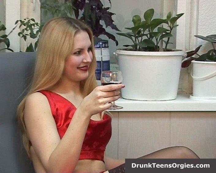 Милая блондинка перед тем как трахнуться пьет стакан алкогольного пойла и мастурбирует пизду