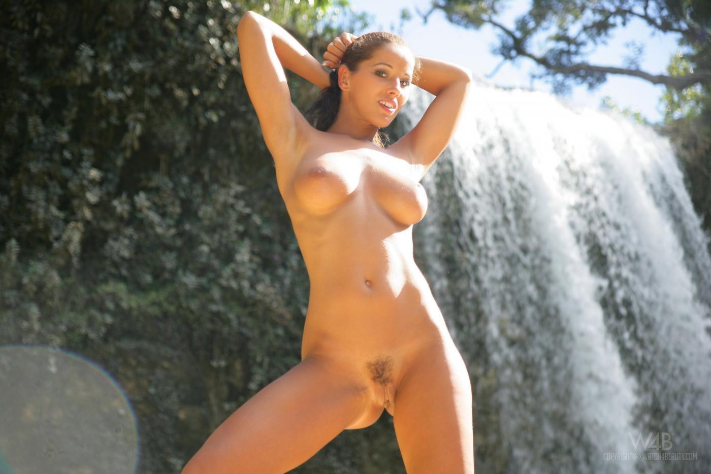 Голый ангел Angel Dark с черными сырыми волосами показывает свою подстриженную пизду и ослепительные груди возле водопада