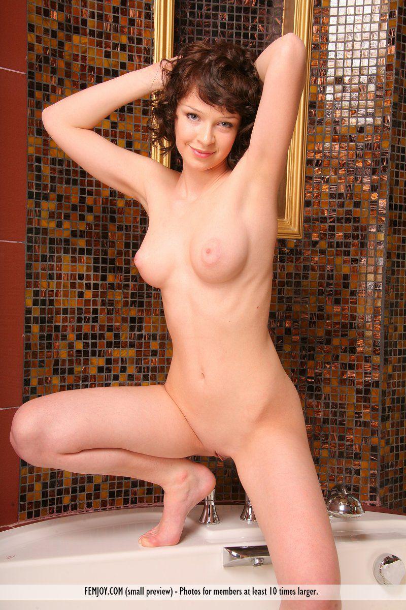 Кудрявая тёмненькая Piroska Femjoy показывает свое голое тело и широко растопыривает ноги в ванне